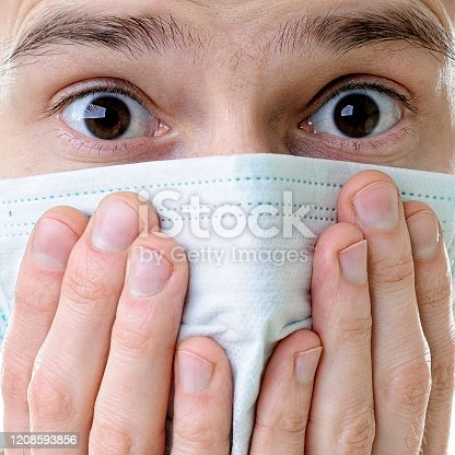 Close-up of a man's face in a medical protective mask isolated on white background.