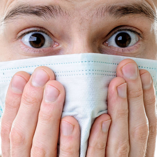 Close-up of a man's face in a medical protective mask stock photo