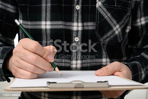 A close-up of a man's hand signing a document with a clipboard.