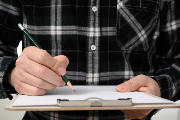 A close-up of a man's hand signing a document with a clipboard stock photo