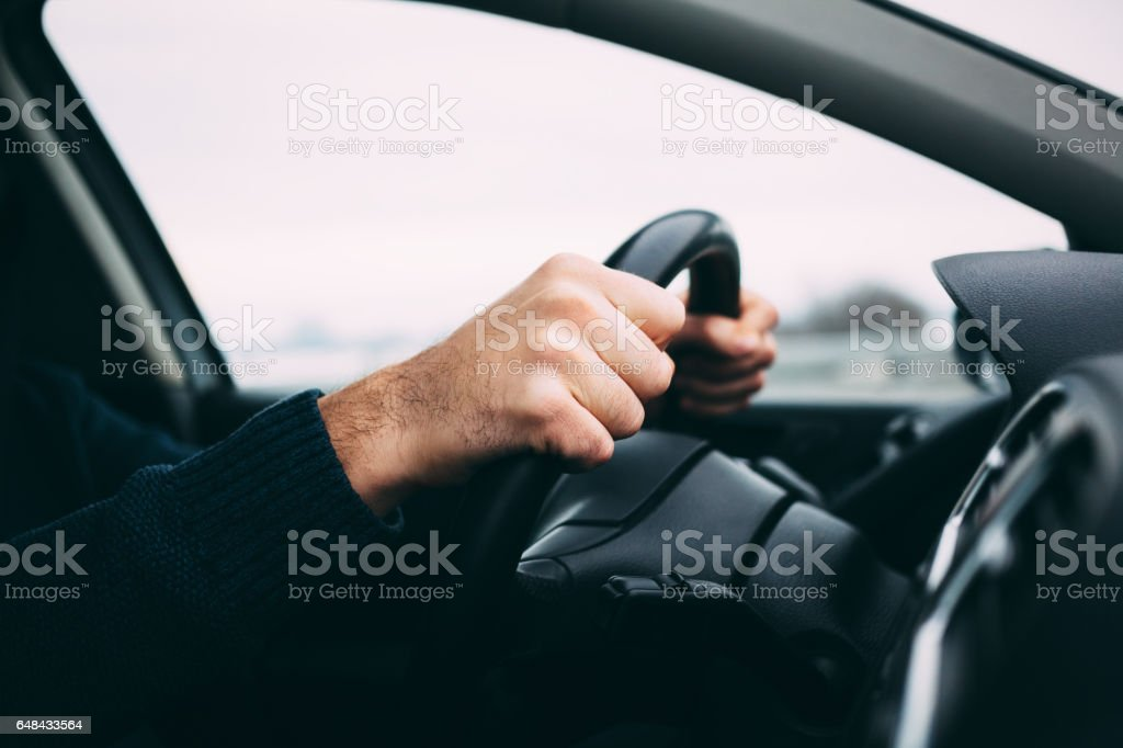 Close-up of a man's hands driving a car stock photo