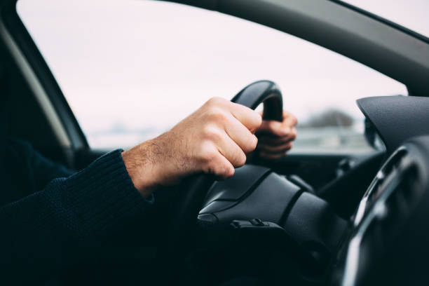 close-up of a man's hands driving a car - knuckle stock photos and pictures