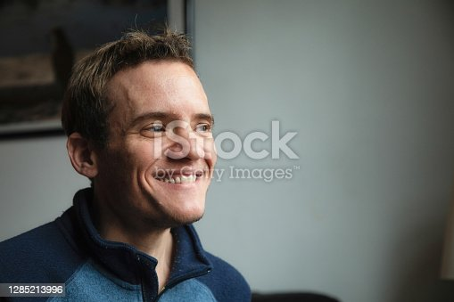 Close-up of a mature autistic man at home smiling as he looks away.