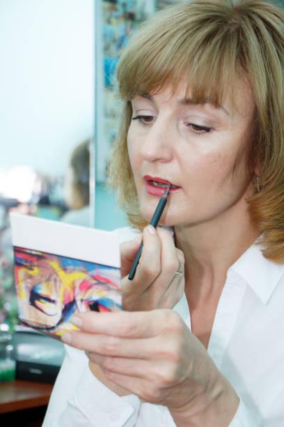 nahaufnahme einer reifen blonden frau tun gesicht make-up, selektiven fokus - natürliche make up kurse stock-fotos und bilder