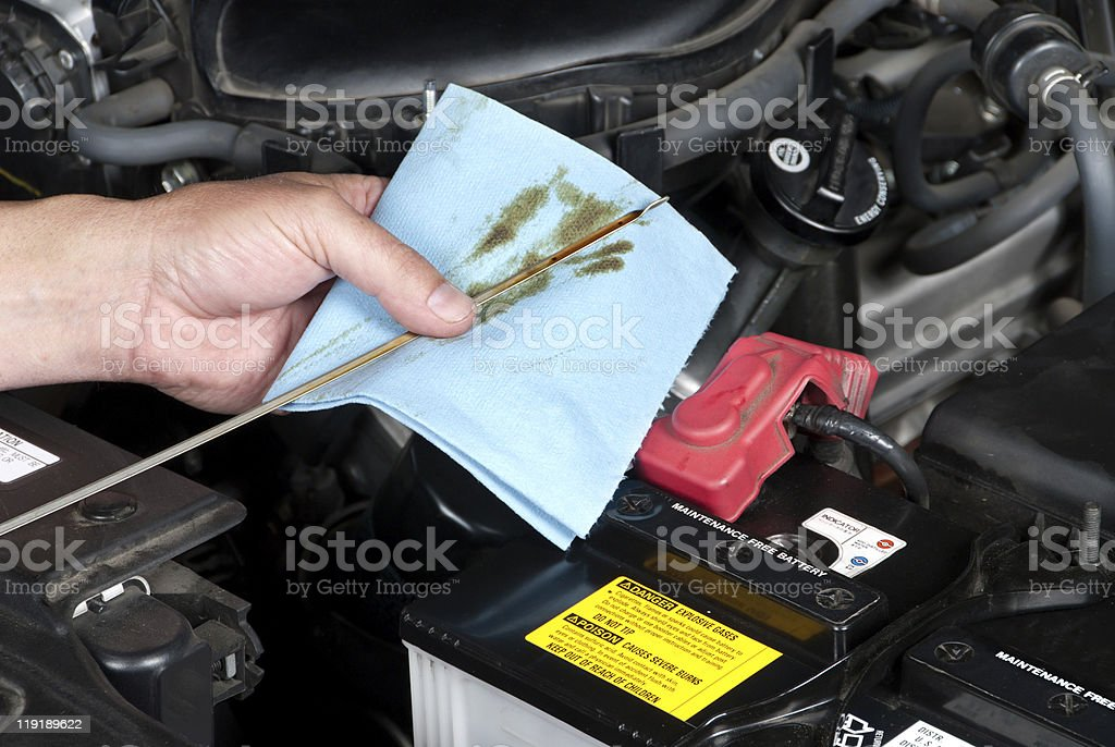 Close-up of a mechanic checking the oil in a car stock photo