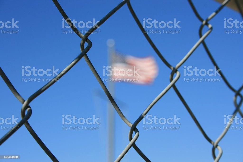 Close-up of a metal fence with a blurred American flag stock photo