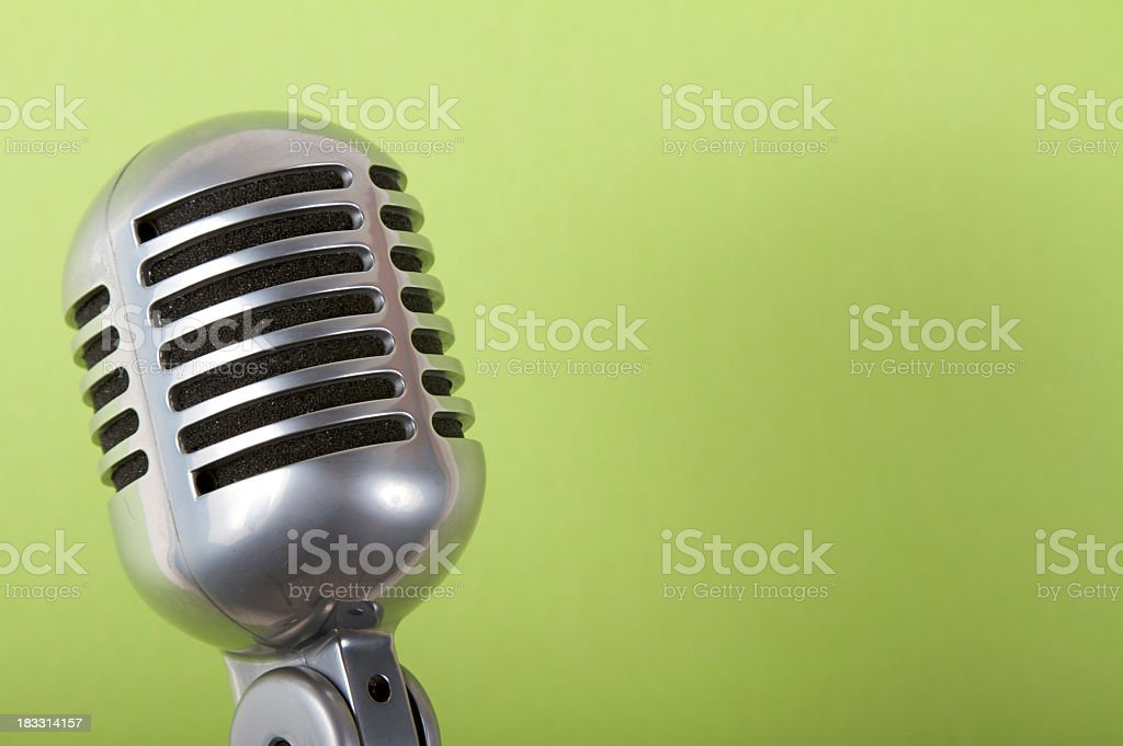 Close-up of a microphone on a green background stock photo