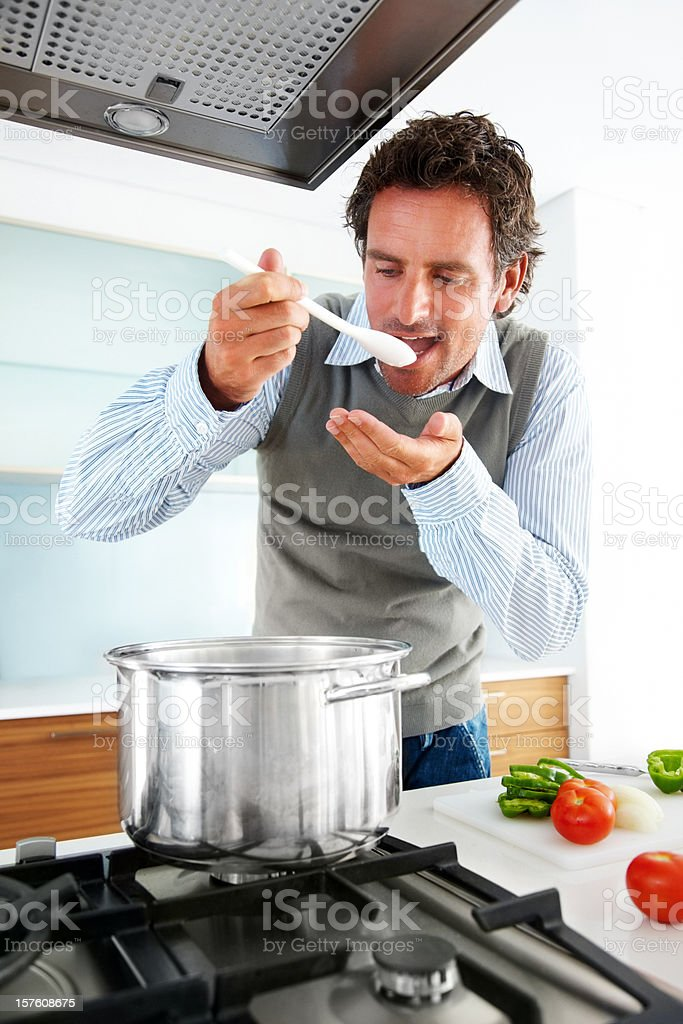 Closeup of a mid adult man tasting food in kithcen royalty-free stock photo