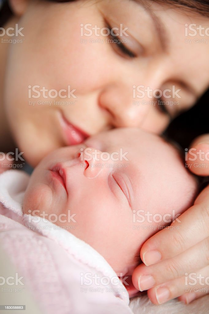 A closeup of a mother kissing her sleeping newborn baby royalty-free stock photo