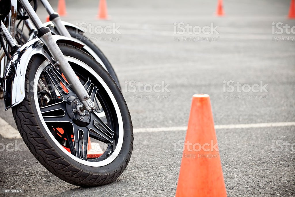 Close-up of a motorcycle wheel near an orange cone stock photo