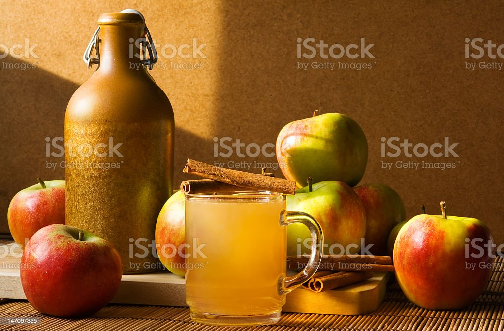 Close-up of a mug with cider next to a jug and some apples royalty-free stock photo
