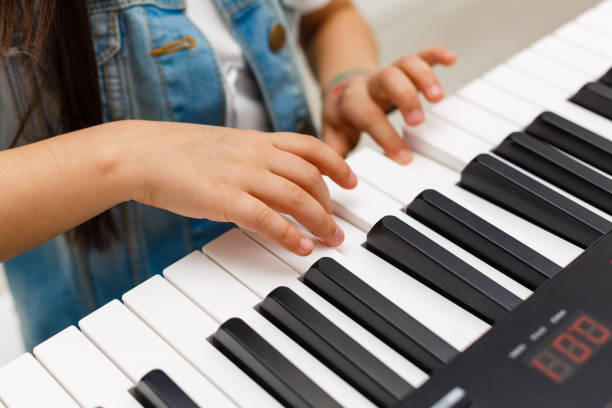 Close-up of a music performer's hand playing the piano Close-up of a music performer's hand playing the piano keyboard player stock pictures, royalty-free photos & images