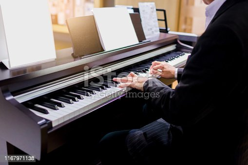 Close-up of a music performer's hand playing the piano. Side view of instrument musical tool. Close up to the piano keyboard background with selective focus. Classical music with black and white key.