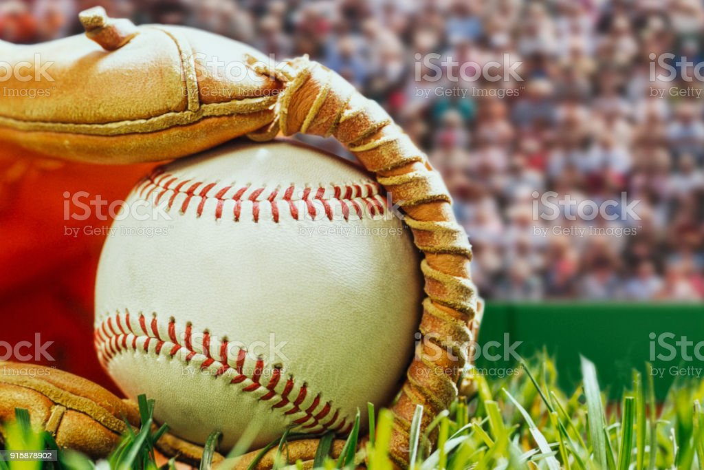 Close-up of a new baseball in a glove in the grass with spectators. stock photo