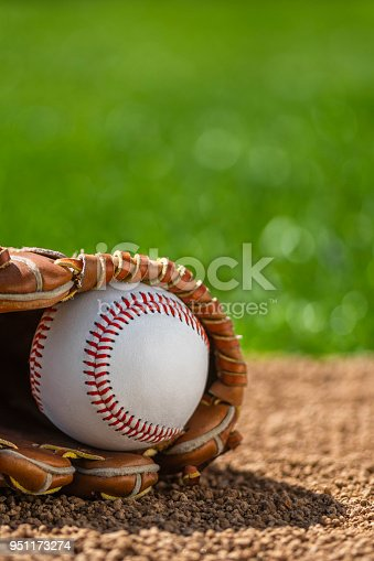 A low angle close-up view of a new baseball in a brown leather baseball glove sitting in the dirt with grass in the background