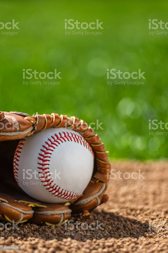 A close-up of a new baseball in a sports glove sitting in the dirt stock photo