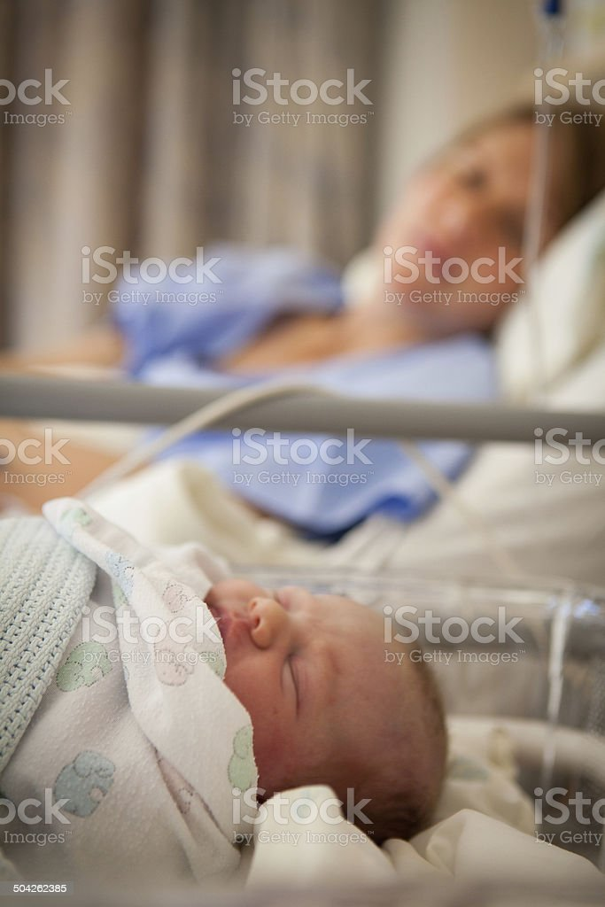 Closeup of a newborn child and her mother in background stock photo