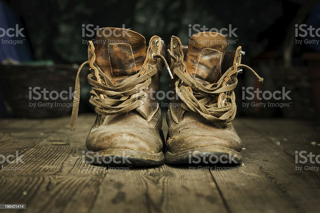 Close-up of a pair of old brown boots on a wooden floor stock photo