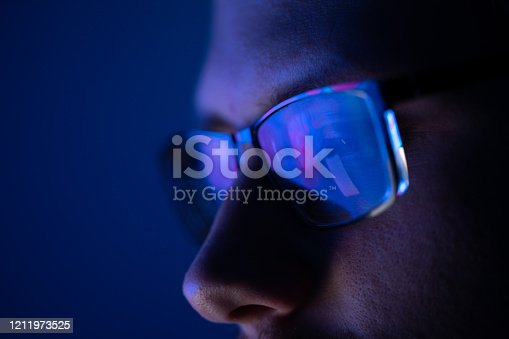 istock Close-up of a part of a male human face with glasses in neon light 1211973525