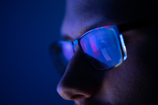 Close-up of a part of a male human face with eyeglasses in neon glow on a background of the vibrant colored liquid