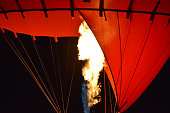 Close-up of a part of red hot air balloon burner flame glowing at night