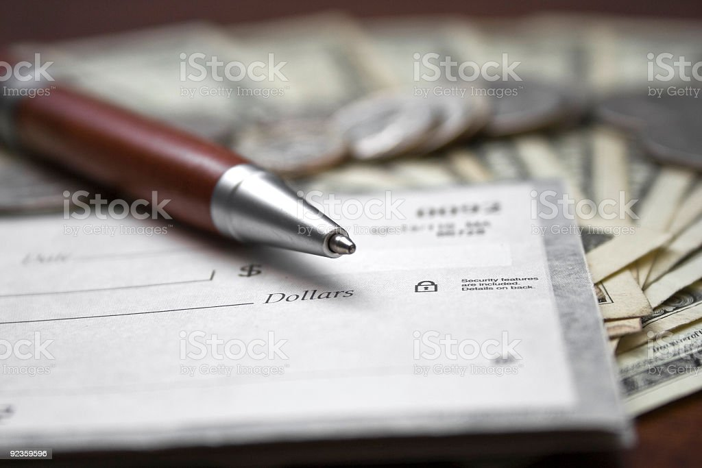Close-up of a pen and check book on top of dollar bills stock photo