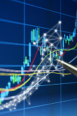 Close-up of a Pen Pointing at Upward Arrow Network Graphic on Digital Stock Market Chart