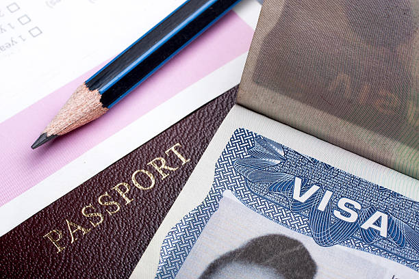 Close-up of a pencil, a passport and a visa document stock photo