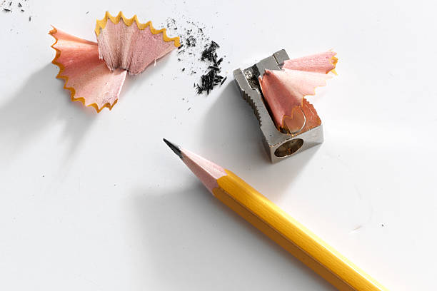 close-up of a pencil and a sharpener with pencil shavings - scherp stockfoto's en -beelden