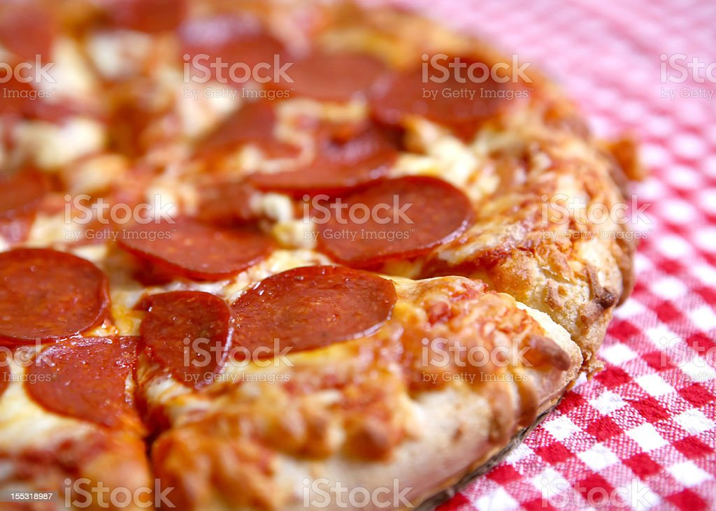 Closeup of a pepperoni pizza on a checkered tablecloth royalty-free stock photo