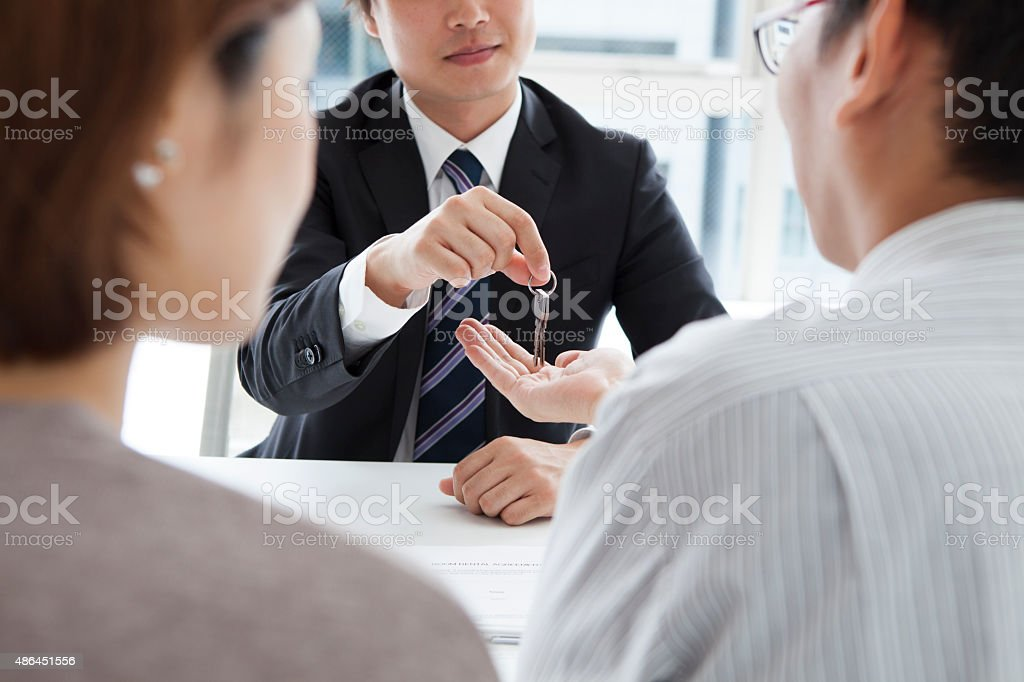 Close-up of a Person giving key to couple stock photo