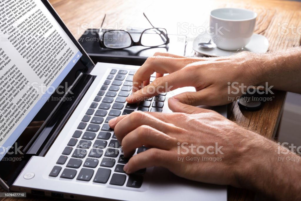 Close-up Of A Person Typing On Laptop stock photo