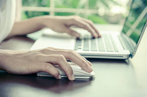 Close-up of a person using a laptop and mouse stock photo