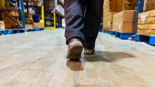 Nahaufnahme der Füße einer Person, die in einem Logistiklager spazieren geht – Foto
