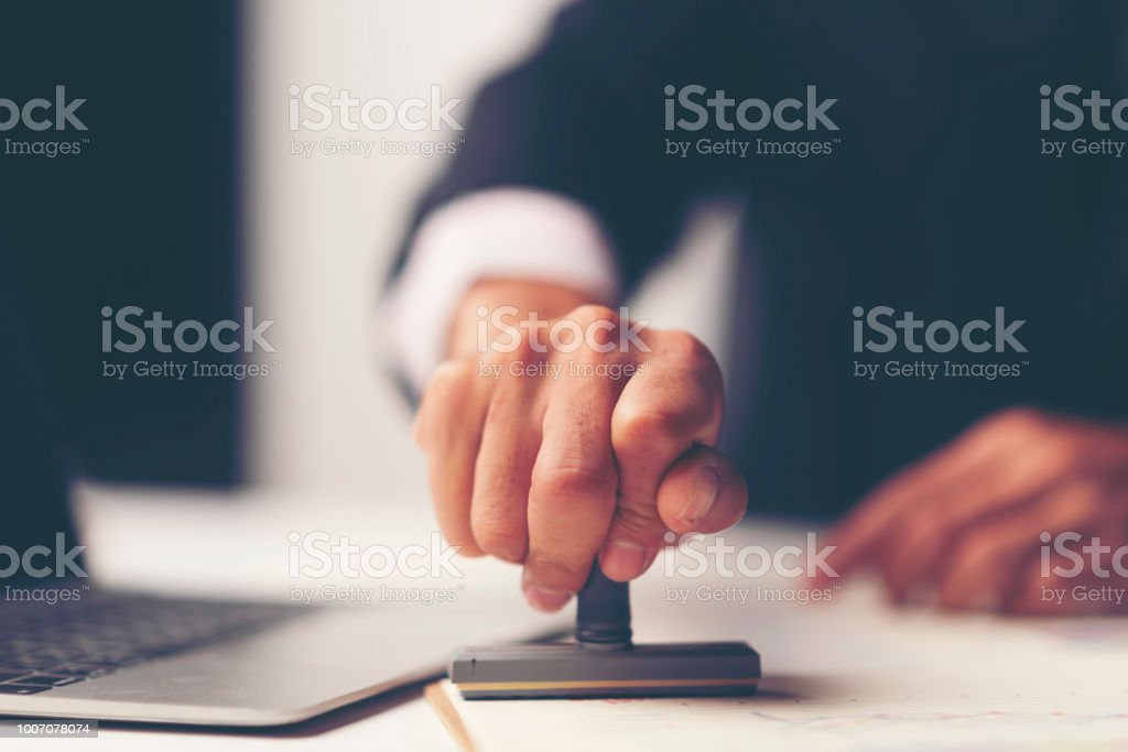 Close-up Of A Person's Hand Stamping With Approved Stamp On Document At Desk Close-up Of A Person's Hand Stamping With Approved Stamp On Document At Desk Adult Stock Photo