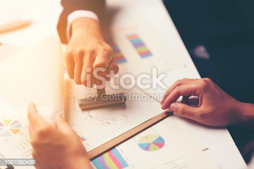 1007078074 istock photo Close-up Of A Person's Hand Stamping With Approved Stamp On Document At Desk 1007080436