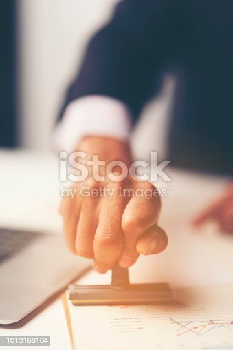 1007078074 istock photo Close-up Of A Person's Hand Stamping With Approved Stamp On Document At Desk 1013168104