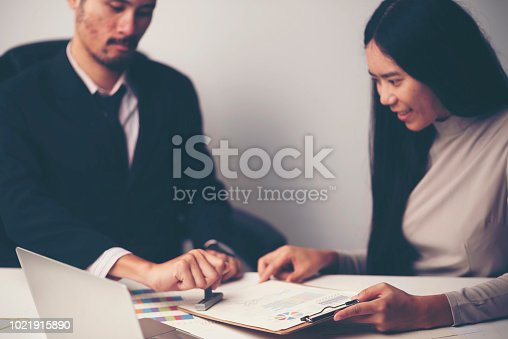 1007078074 istock photo Close-up Of A Person's Hand Stamping With Approved Stamp On Document At Desk 1021915890