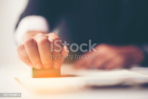 1007078074 istock photo Close-up Of A Person's Hand Stamping With Approved Stamp On Document At Desk 1021918574