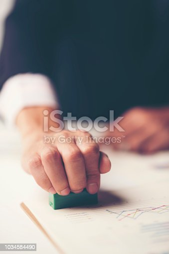 1007078074 istock photo Close-up Of A Person's Hand Stamping With Approved Stamp On Document At Desk 1034584490