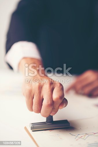 1007078074 istock photo Close-up Of A Person's Hand Stamping With Approved Stamp On Document At Desk 1034587026