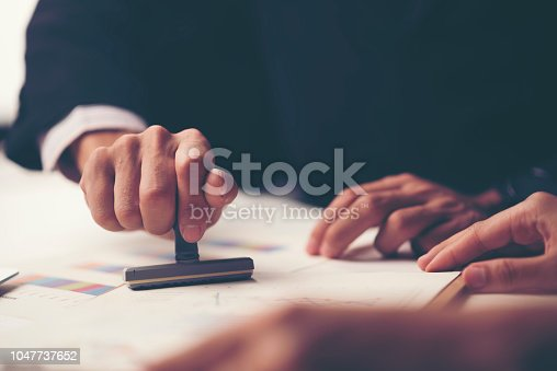 1007078074 istock photo Close-up Of A Person's Hand Stamping With Approved Stamp On Document At Desk 1047737652