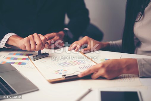 1007078074 istock photo Close-up Of A Person's Hand Stamping With Approved Stamp On Document At Desk 1047737812