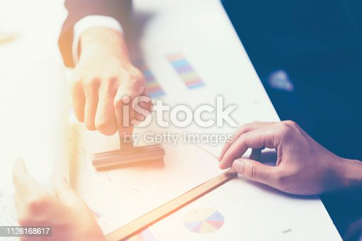 1007078074 istock photo Close-up Of A Person's Hand Stamping With Approved Stamp On Document At Desk 1126168617