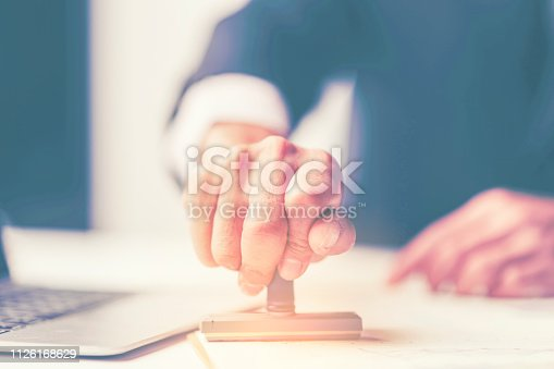 1007078074 istock photo Close-up Of A Person's Hand Stamping With Approved Stamp On Document At Desk 1126168629