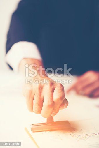 1007078074 istock photo Close-up Of A Person's Hand Stamping With Approved Stamp On Document At Desk 1126168689