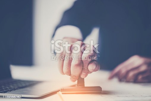 1007078074 istock photo Close-up Of A Person's Hand Stamping With Approved Stamp On Document At Desk 1159566282