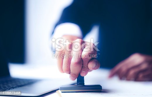 1007078074 istock photo Close-up Of A Person's Hand Stamping With Approved Stamp On Document At Desk 1159573468