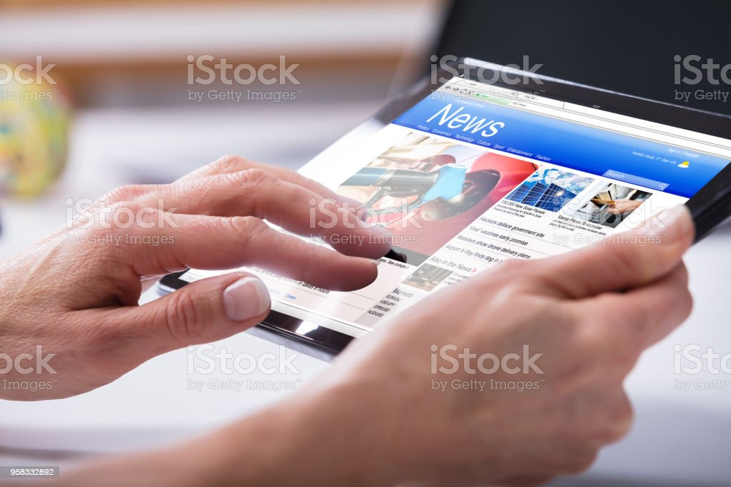 Close-up Of A Person's Hand Using Digital Tablet stock photo