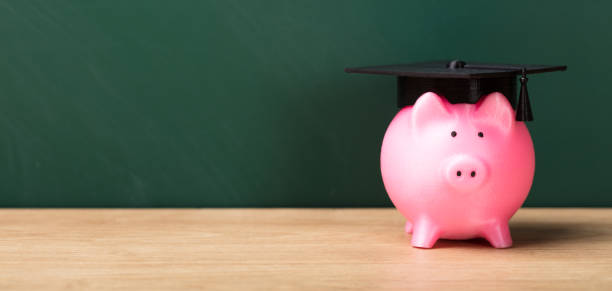 Close-up Of A Piggy Bank With Graduation Cap Close-up Of A Piggy Bank With Graduation Cap In Front Of Green Chalkboard 40 kilometre stock pictures, royalty-free photos & images